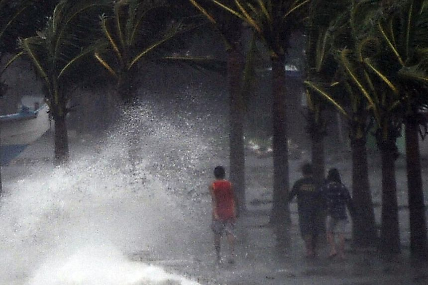Residents walk past high waves brought about by strong winds as it pound the seawall, hours before Typhoon Hagupit passes near the city of Legazpi on Dec 7, 2014. Typhoon Hagupit tore apart homes and sent waves crashing through coastal communities ac