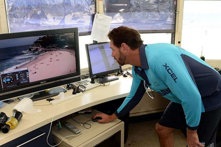 """Australia's best known lifeguard Bruce """"Hoppo"""" Hopkins monitoring different parts of beaches on close circuit camres at Bondi Beach in Sydney on Oct 28, 2014. -- PHOTO: AFP"""