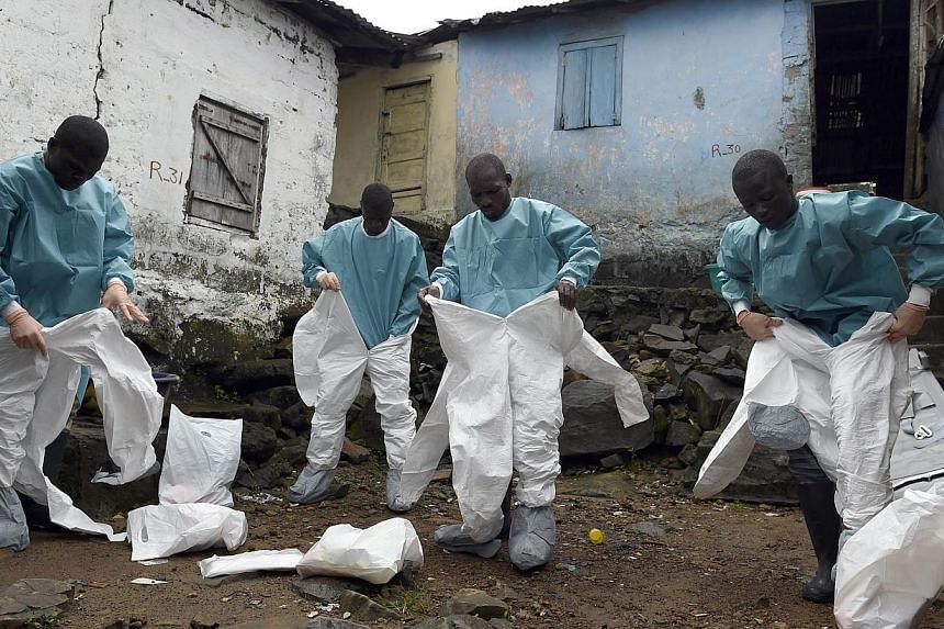 Medical staff members of the Croix Rouge NGO put on protective suits before collecting the corpse of a victim of Ebola, in Monrovia, on Sept 29, 2014.A Taiwanese man faces a fine after telling doctors in Kaohsiung he had travelled to Africa and