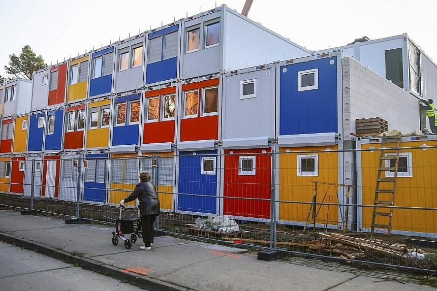 Workers fix containers at a construction site for a refugee centre to house asylum seekers in Berlin on Nov 27, 2014.German businesses would like to see asylum seekers given quicker access to the jobs market, saying they could benefit Europe's
