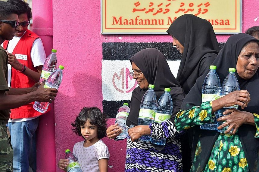 Maldives residents receive their supply of water distributed by Red Crescent and security personnel after a fire at a desalination plant affected water supplies in Male, on Dec 5, 2014. Maldivian President Abdulla Yameen cut short his trip to Ma