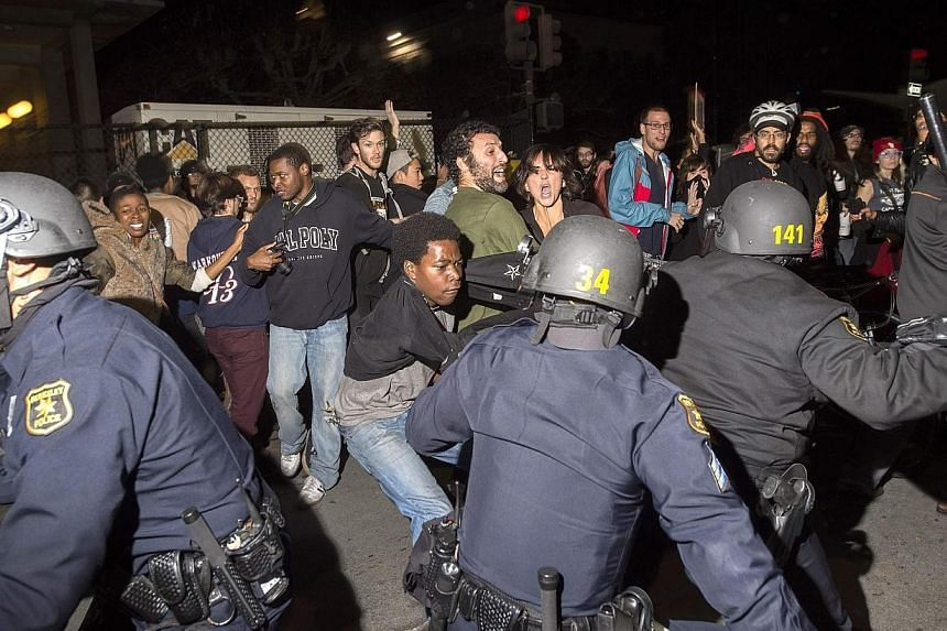 Police officers scuffle with protesters during a protest against police violence in Berkeley, California on Dec 6, 2014.Protests in California against a spate of recent killings of young African American suspects turned violent, as demonstrator