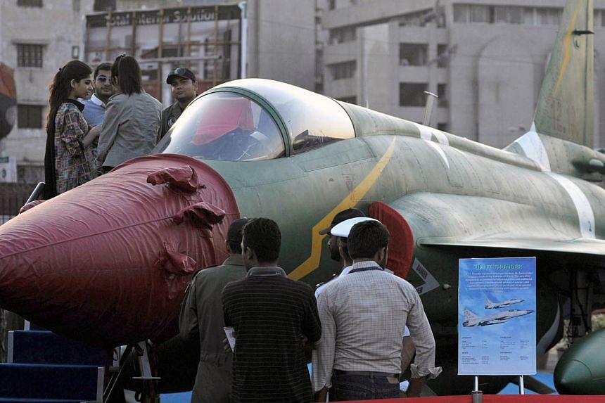 Visitors look at a PAC JF-17 Thunder multirole combat aircraft, conceived and initially developed with the help of China, on static display at the International Defence Exhibition and seminar (IDEAS) in Karachi on Dec 3, 2014. A revamped version