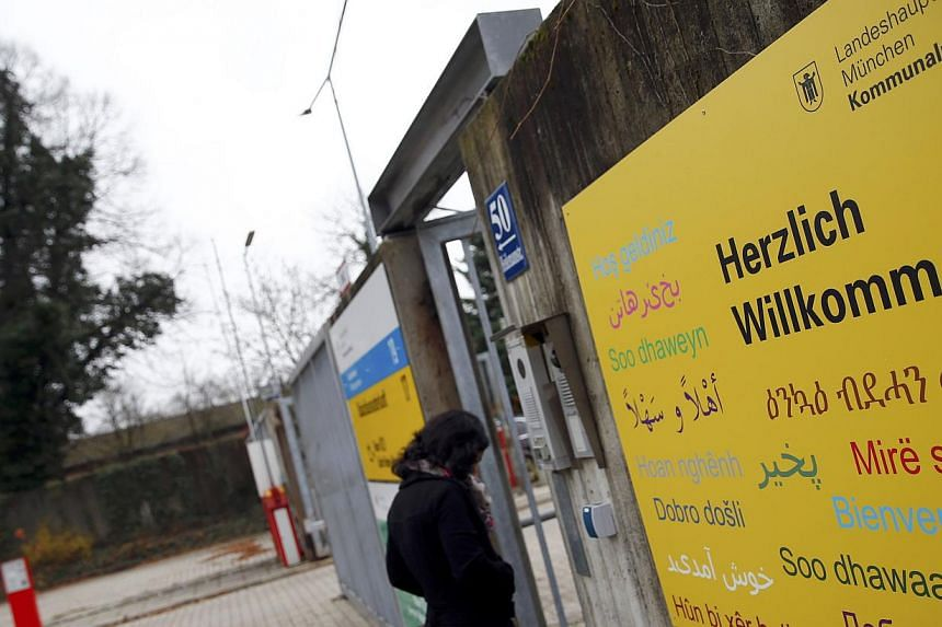 """A woman walks inside the former German army base """"Bayernkaserne"""" which has been converted into a refugee camp in Munich on Nov 20, 2014.German Chancellor Angela Merkel's Bavarian allies have issued a call for immigrants to speak German at home,"""