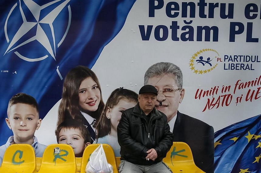 A man sits in front of a pre-election poster for the Liberal Party in Chisinau, Moldova, on Nov 29, 2014.German Chancellor Angela Merkel accused Russia on Sunday of interfering in the domestic affairs of numerous countries, including Moldova, t
