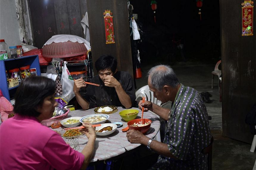 Mr Chu, his wife and brother-in-law having dinner at the end of the day. Meals on the island are usually kept simple. Residents also make regular trips back to the mainland to shop for groceries at the Changi Village market. -- ST PHOTO: DESMOND LIM