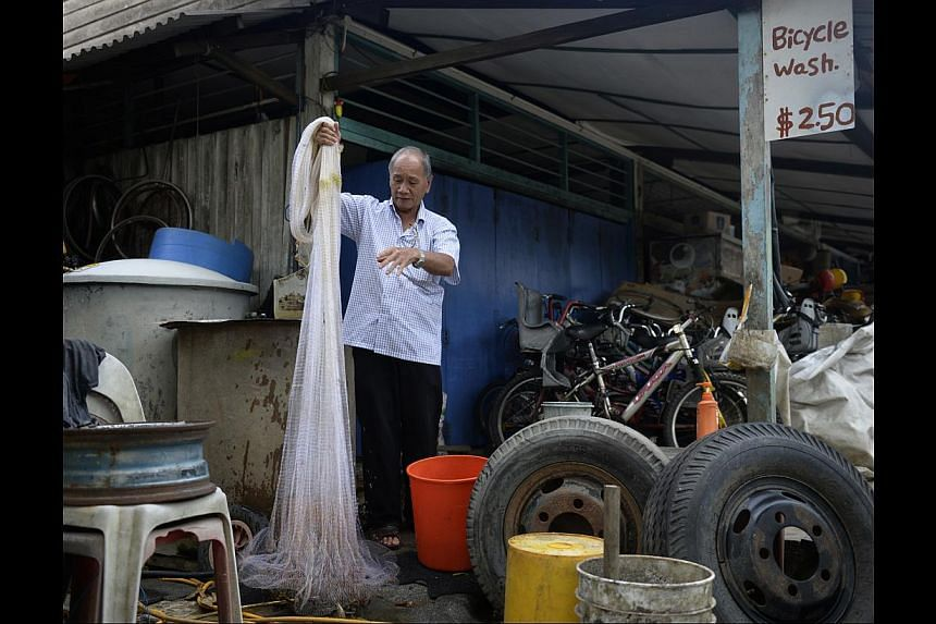 """Mr Chu, an avid fisherman, washes his fishing net (above) after closing his shop, and checks his net for catches. He cherishes the freedom island life gives him. """"I can fish anytime I want to,"""" he says. -- ST PHOTO: DESMOND LIM"""