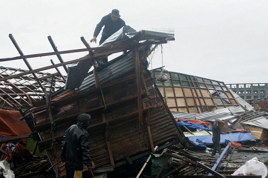 A man is seen on top of his damaged house in Tacloban, central Philippines on Dec 7, 2014. A powerful, slow-moving typhoon ripped through the central Philippines on Sunday, bringing howling winds that flattened houses and toppled trees and power