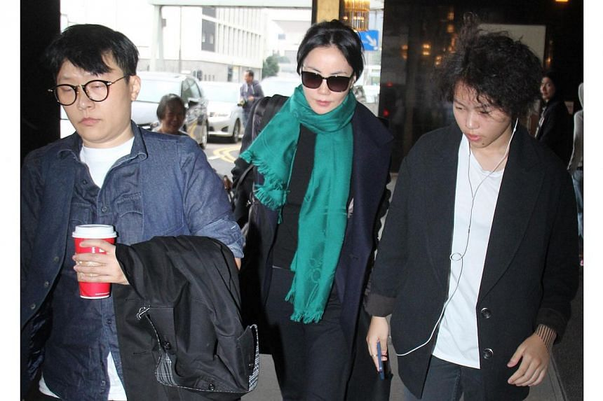 Wong and her daughter on their way to the Mandarin Oriental. A stripy tattoo is visible on Dou's left hand. -- PHOTO: APPLE DAILY