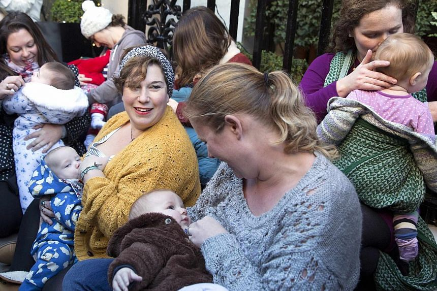 Demonstrators feed their babies during a protest in support of breastfeeding in public, outside Claridge's hotel in London Dec 6, 2014. -- PHOTO: REUTERS