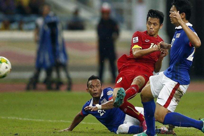 Vietnam's Nguyen Van Quyet (centre) scores the winning goal of the match during the first leg of the AFF Suzuki Cup 2014 semi-final first leg against Malaysia at the Shah Alam stadium in Selangor on December 7, 2014. -- PHOTO: REUTERS