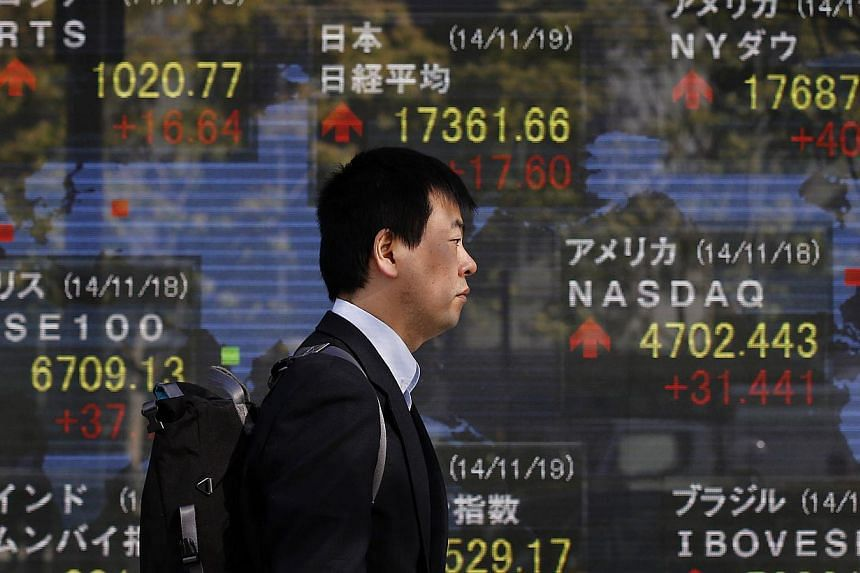 A man walks past an electronic board showing the stock market indices of various countries, outside a brokerage in Tokyo. A Japanese government spokesman said on Monday there is no change in the government's view that the economy is continuing to rec