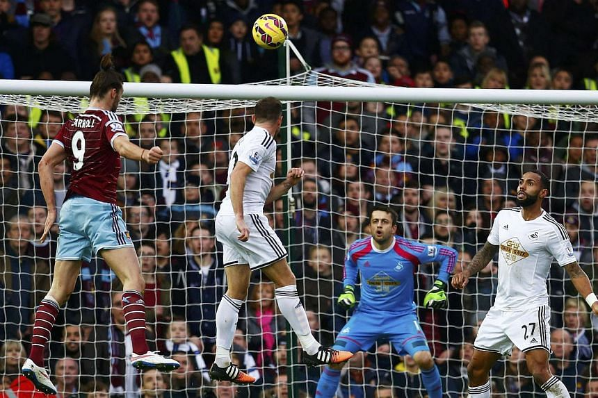 Andy Carrol (left)l of West Ham United heads to score against Swansea City during their English Premier League match against Swansea at Upton Park in London on Dec 7, 2014. -- PHOTO: REUTERS