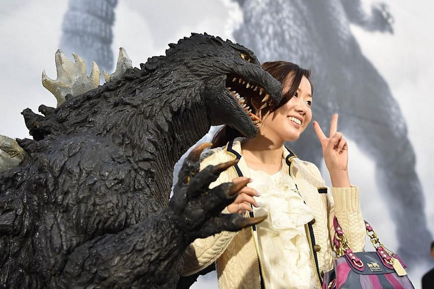 Japan's star monster Godzilla (front left) poses with a fan after an awards ceremony at Toho Studio in Tokyo's Setagaya Ward on Nov 3, 2014. -- PHOTO: AFP