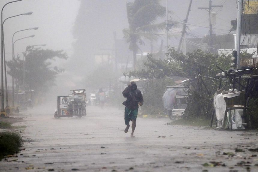 A man walks on a street while strong winds and heavy rain, brought by typhoon Hagupit, batter Atimonan town, Quezon province, south of Manila on Dec 8, 2014. A typhoon that struck the Philippines over the weekend has claimed at least 21 lives, t
