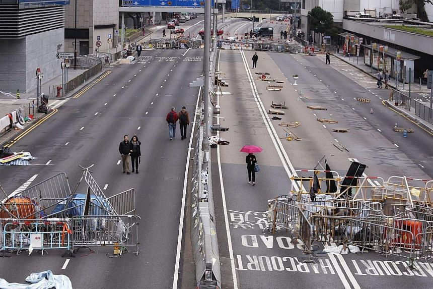 People walk past obstacles and barricades set up by pro-democracy protesters on a main road at the financial Central district in Hong Kong on Dec 7, 2014. Hong Kong pro-democracy protesters were thin on the ground on Dec 8, ahead of a possible m