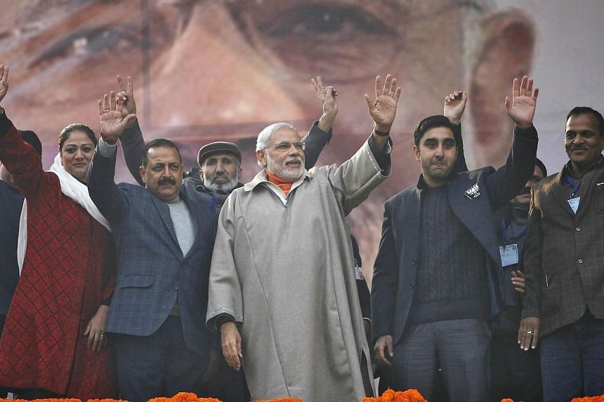 India's Prime Minister Narendra Modi (centre) waves to the crowd after he addressed an election campaign rally in Srinagar on Dec 8, 2014.Mr Modi promised to bring prosperity to Indian Kashmir and told people not to be intimidated against votin