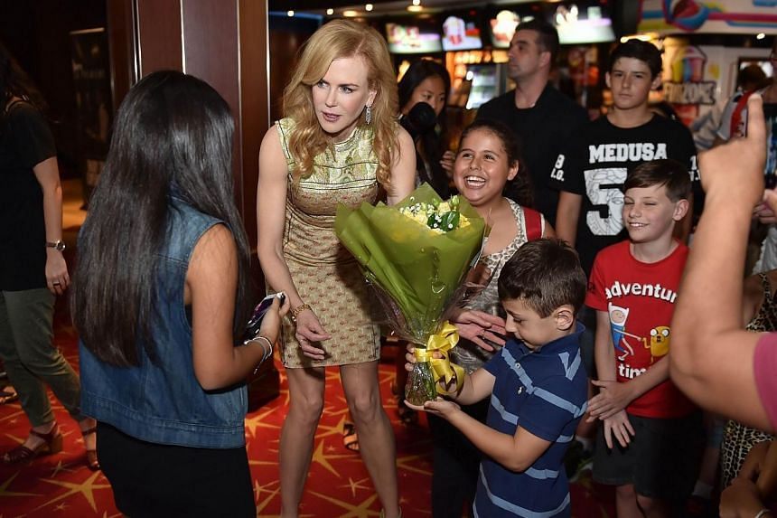 Australian actress Nicole Kidman (second from left) talks to kids before a special screening of her new film Paddington for children being treated at Sydney Children's Hospital on Dec 8, 2014. -- PHOTO: AFP