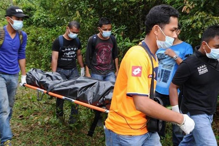 Plainclothes police carrying remains believed to be that of a Myanmar national earlier in 2014 in Penang, Malaysia. In yet another case on Penang island, a man believed to be a foreigner was found with his throat slit and several stab wounds on his b