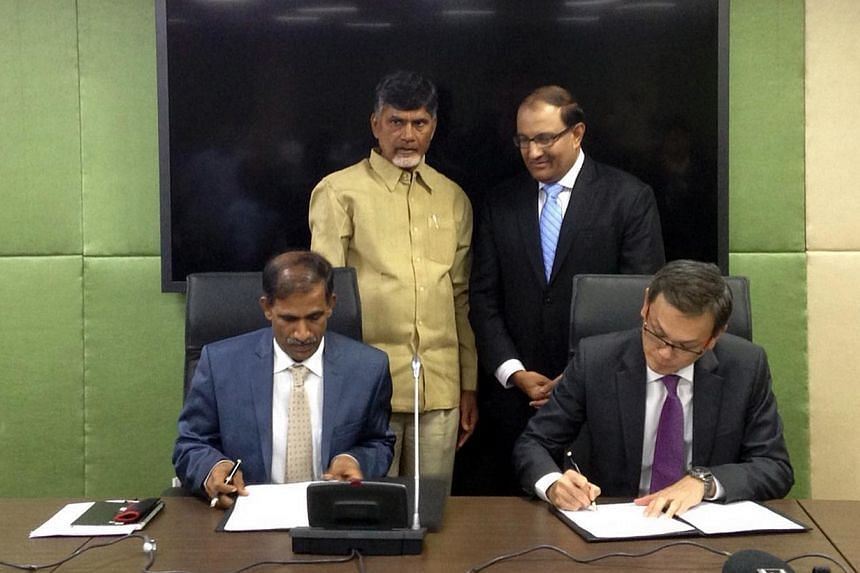 International Enterprise Singapore CEO, Mr Teo Eng Cheong (seated, right), and the Infrastructure Corporation of the Andhra Pradesh representative, Dr Sambasiva Rao (seated, left), signing a memorandum of understanding on Dec 8, 2014, to pr