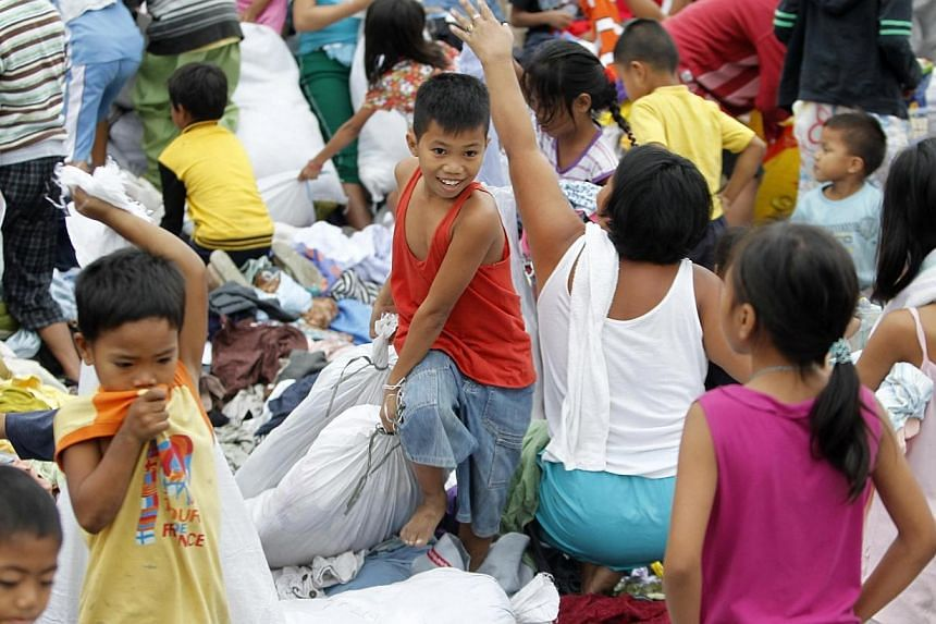 A boy pulls a sack of donated clothes at an evacuation centre for the coastal community, to shelter from typhoon Hagupit, in Manila, on Dec 8, 2014. -- PHOTO: REUTERS
