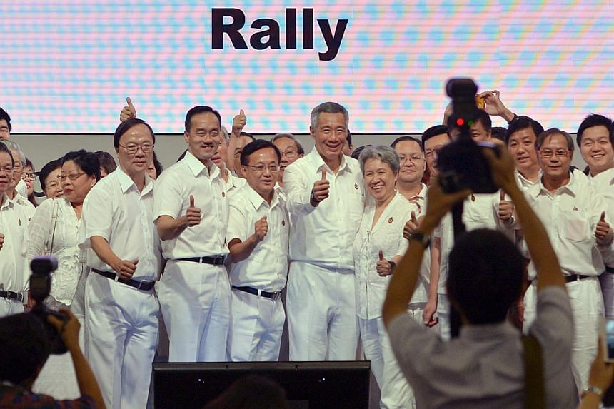 Prime Minister Lee Hsien Loong and his wife Ho Ching with former PAP Punggol East candidate Koh Poh Koon (fourth from left), Ang Mo Kio GRC MP Seng Han Thong (fifth from left) and PAP grassroots activists after the PAP rally yesterday. -- ST PHOTO: C