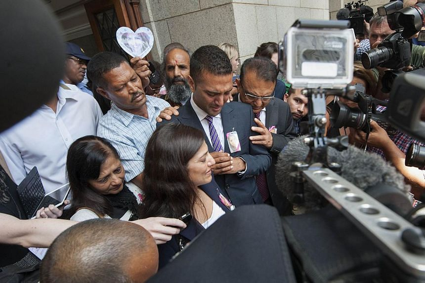 Anish and Vinod Hindocha (left and right) brother and father of murdered tourist, Anni Dewani face the waiting media, after Dewani's husband Shrien Dewani (not visible) was acquitted of her murder on Dec 8, 2014, in Cape Town.-- PHOTO: AFP