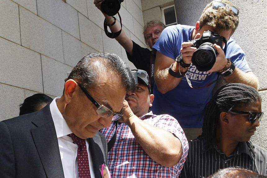 Vinod Hindocha, father of murdered Anni Dewani, leaves the court with family members in Cape Town on Dec 8, 2014.-- PHOTO: REUTERS