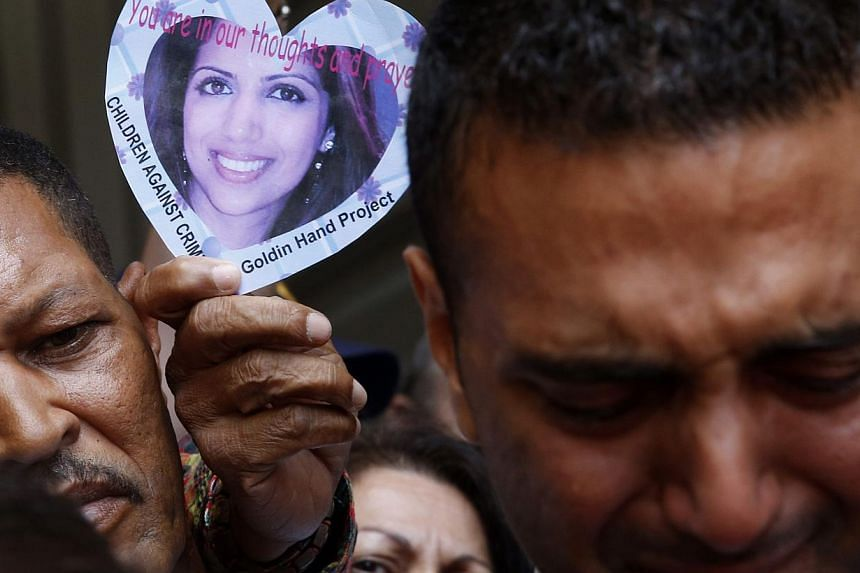 A supporter holds a picture of Anni Dewani as Anni's brother Anish Hindocha (right) leaves a court with family members in Cape Town on Dec 8, 2014.-- PHOTO: REUTERS