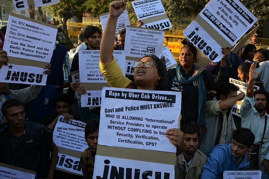 Indian residents hold placards and chant slogans as they take part in a protest against the alleged rape of a passenger by a driver working for the Uber taxi company in New Delhi on Dec 7, 2014. -- PHOTO: AFP