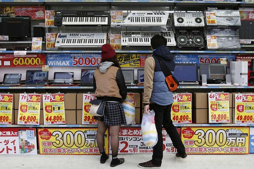 People try out laptops displayed at an electronics retail store in Tokyo on Nov 16, 2014. Japan releases its final 3Q GDP data on Monday. -- PHOTO: REUTERS
