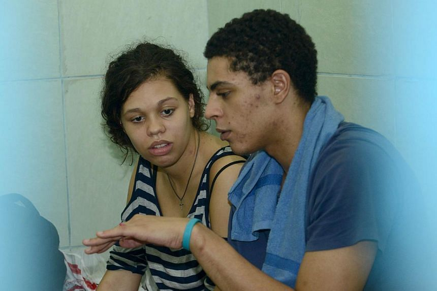 Heather Mack (left) of the US speaks with her boyfriend Tommy Schaefer (right) inside a holding cell at the procecutor's office in Denpasar on Indonesia's resort island of Bali on Dec 8, 2014. -- PHOTO: AFP