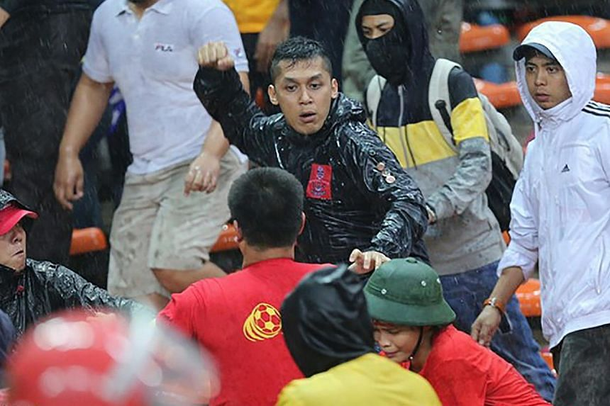 A Malaysian fan beating up rival Vietnamese supporters after Vietnam won 2-1 against Malaysia in their AFF Suzuki Cup semi-final first leg at Shah Alam stadium on Dec 7, 2014. -- PHOTO: ZING