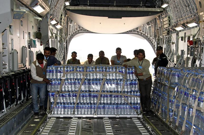 Indian workers and Air Force personnel load emergency supplies of bottled water onto a Boeing C-17 heavy transport aircraft in New Delhi, bound for the Maldives, after a fire at a desalination plant affected water supplies in Male, on Dec 5, 2014. Re