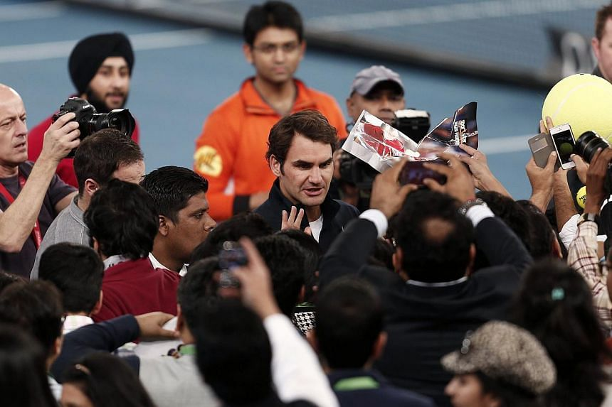 Roger Federer (centre) of the Micromax Indian Aces signs autograph after winning his men's single match against TomasBerdych of the Singapore Slammers at the International Premier Tennis League in New Delhi on Sunday. -- PHOTO: REUTERS