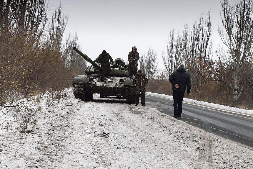 Donestk People's Republic (DNR) fighters stand by their tank on Dec 7, 2014 in the eastern Ukrainian Donesk region. Eight civilians have been killed in fresh violence in eastern Ukraine, where more explosions and gunfire rang out on two days before t