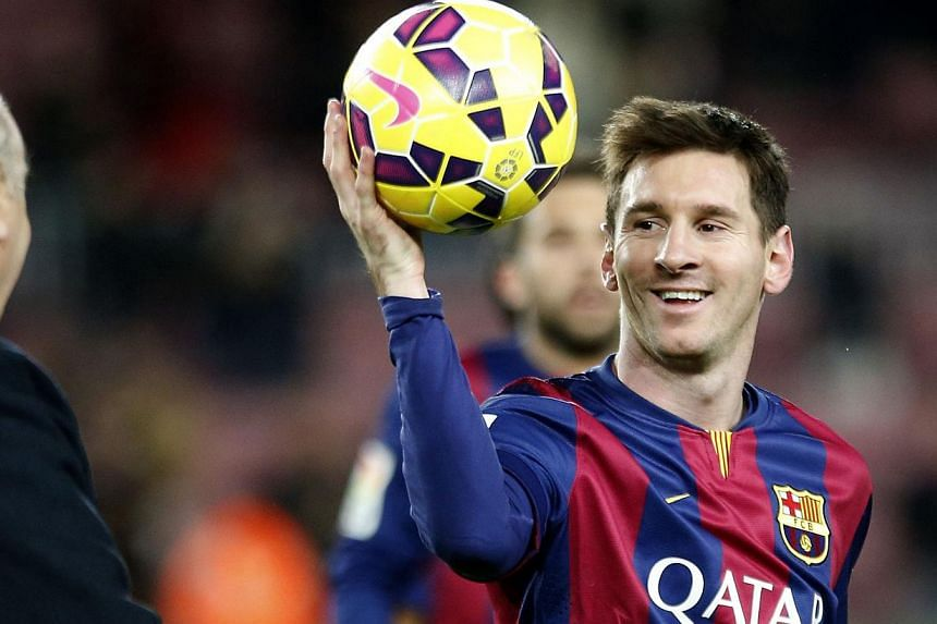 Barcelona's Lionel Messi collects the ball after scoring his hat trick against Espanyol during their Spanish first division soccer match at Nou Camp stadium in Barcelona on Dec 7, 2014. -- PHOTO: REUTERS