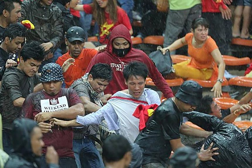 Malaysian fans clash with Vietnamese fans after Vietnam won 2-1 against Malaysia in their AFF Suzuki Cup semi-final first leg at Shah Alam stadium on Dec 7, 2014. -- PHOTO: ZING