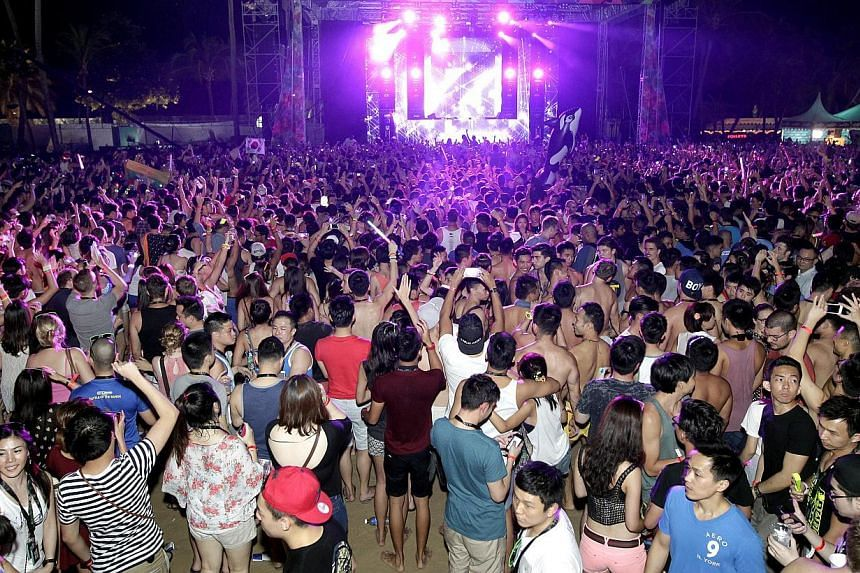 People partying at ZoukOut 2013. Revellers attending ZoukOut 2014 on Dec 12 and 13 are advised to take public transport due to limited parking on Sentosa Island and in anticipation of heavy traffic during the event. -- ST PHOTO: CHEW SENG KIM
