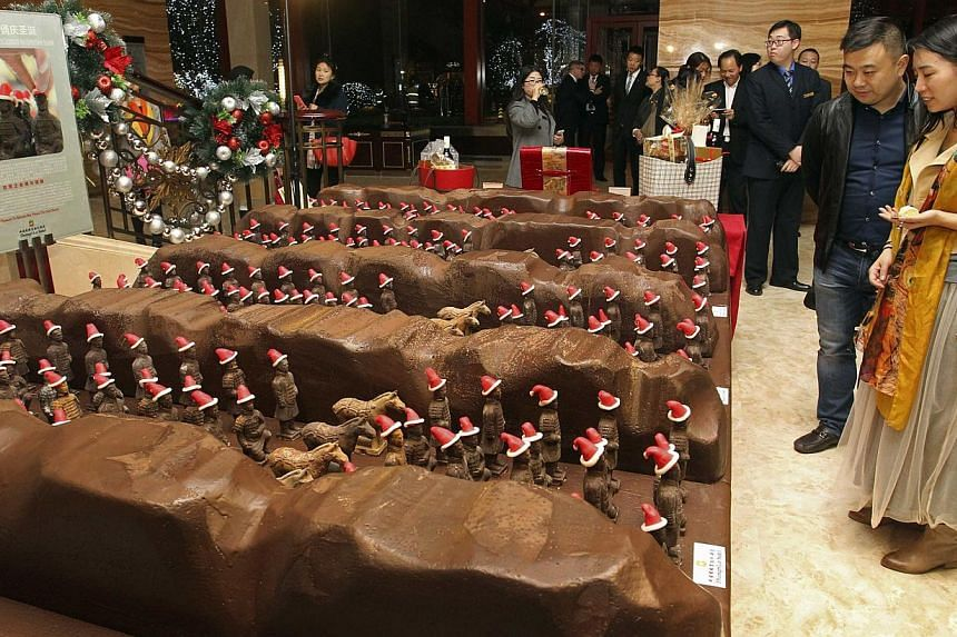 Customers looking at miniature chocolate terracotta warriors wearing Santa Claus hats on display at the lobby of a hotel in Xi'an, China, on Nov 21, 2014. -- PHOTO: REUTERS