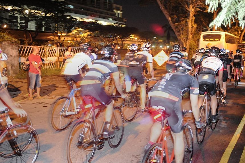 Participants in HolyCrit, an illegal street cycling race, along Tanglin Halt Road. Two men have been arrested by the Traffic Police for their suspected involvement in promoting and organising illegal racing activities along Tanglin Halt Road last mon