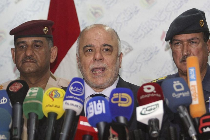 Iraqi Prime Minister Haider al-Abadi (centre) speaks at a news conference in Kerbala, southwest of Baghdad, on Dec 8, 2014.Iraq's Prime Minister pressed outgoing US Defence Secretary Chuck Hagel on Tuesday for more air strikes and weaponry to a