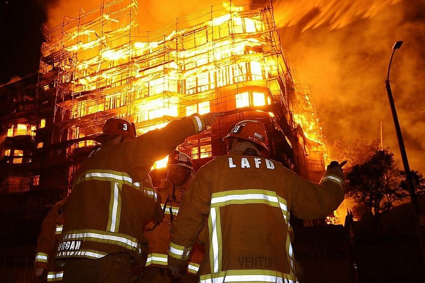 Los Angeles city firefighters battle a massive fire at a seven-story downtown apartment complex under construction in Los Angeles, California on Monday. Over 250 firefighters battle the early morning blaze which shutdown two major freeways. -- PHOTO: