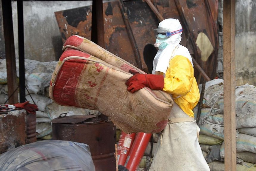 A Guinea's health worker removes a mattress at an Ebola Donka treatment centre in Conakry on Dec 8, 2014. The UN's Ebola czar on Tuesday hailed widespread progress in the fight against the deadly virus, but warned the outbreak was still surging in we