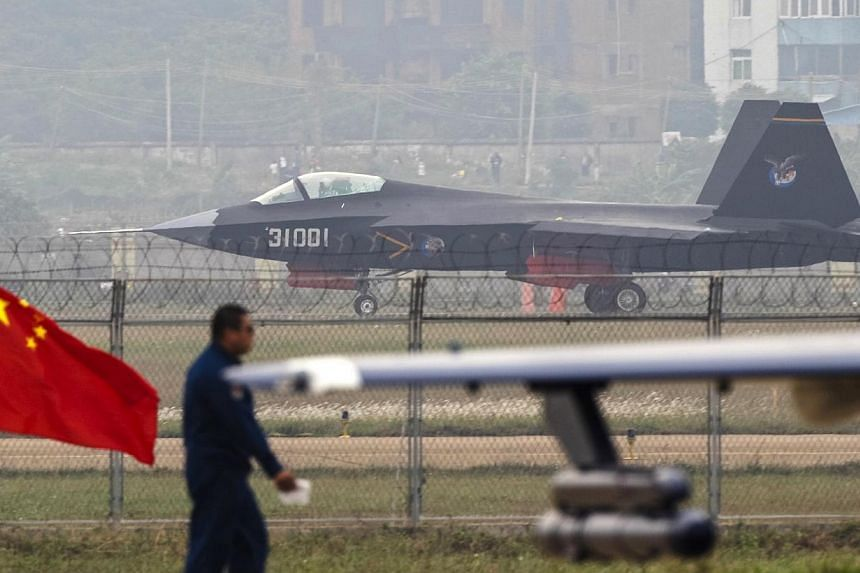 A J-31 stealth fighter (background) of the Chinese People's Liberation Army Air Force lands on a runway after a flying performance at the 10th China International Aviation and Aerospace Exhibition in Zhuhai, Guangdong province, Nov 11, 2014. The pres