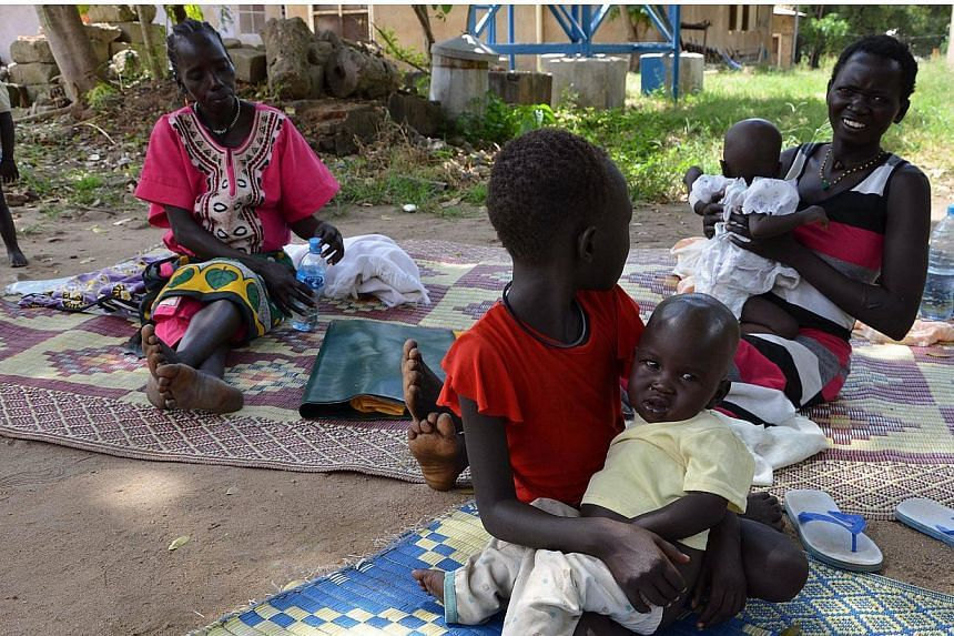 A girl holds her younger brother who is currently treated for malaria and dehydration at the Al Sabbah Children's hospital in Juba on Oct 14, 2014.The number of people dying from malaria has almost halved since 2000, although progress in west A