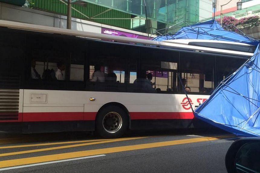 A makeshift tent was displaced from an elevated position and landed on a SMRT bus in Chinatown on Tuesday afternoon. -- PHOTO: FACEBOOK