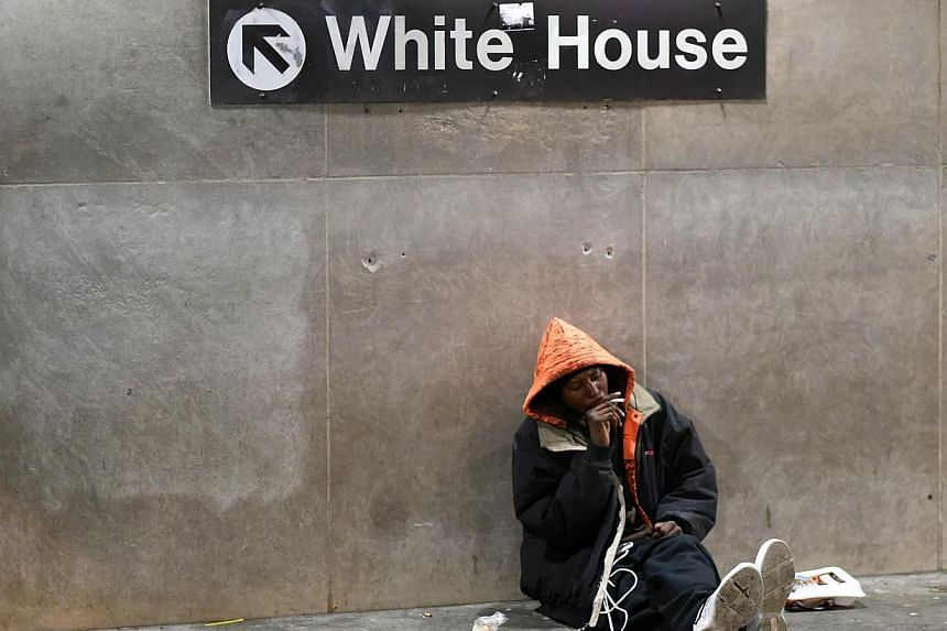 A homeless man sits under a sign giving directions to the White House at the entrance of the McPherson Metro Station in Washington, DC on Nov 25, 2014. -- PHOTO: AFP