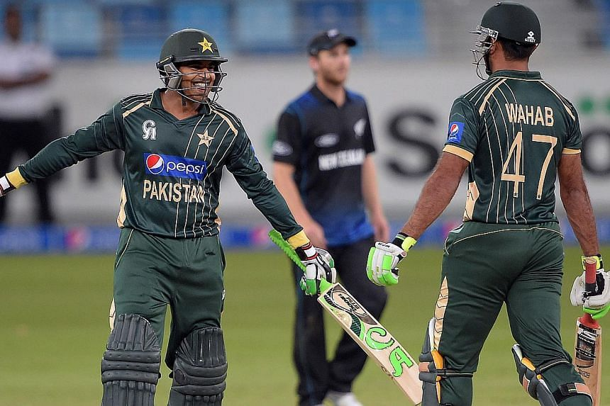 Pakistani batsman Haris Sohail (left) celebrates with teammate Wahab Riaz after playing a winning shot during the first Day-Night International cricket match to steer Pakistan to a three-wicket win over New Zealand in the first day-night internationa