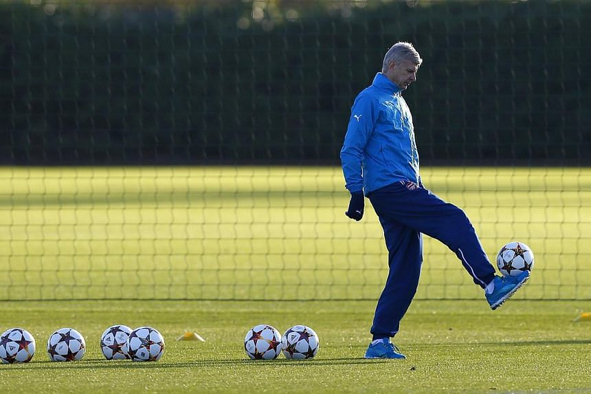 Arsenal manager Arsene Wenger controls a ball during a training session ahead of their Champions League soccer match against Galatasaray, at their training facility in London Colney, north of London on Monday. -- PHOTO: REUTERS